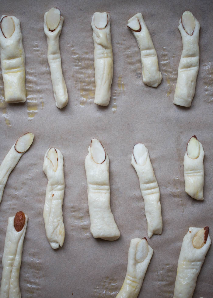 Witch finger will you eat first? Here are two ways to make delightfully creepy witches' fingers breadsticks - use either sliced almonds for the gnarly fingernail or go for bell pepper for a nut-free version. #halloweenfood #severedfingers #witchesfingersbreadsticks