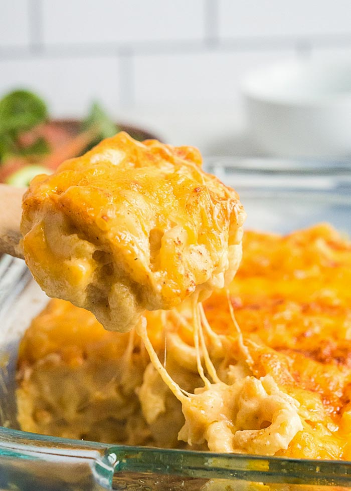 Scooping a big cheesy portion of the best baked macaroni and cheese recipe ever