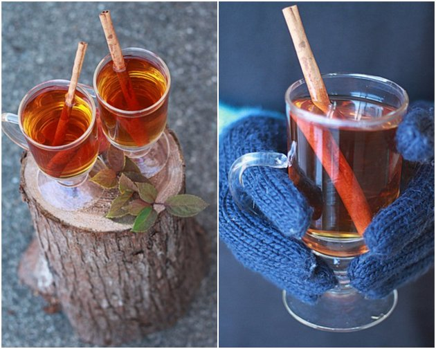 Mugs of hot spiced apple cider on a stump and mittened hands holding a warm mug of cider