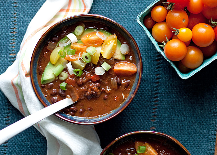 Slow Cooker Black Bean Pumpkin Chili - Black beans, pumpkin, and warming spices simmer together in your Crock Pot to make a vegetarian and vegan pumpkin chili recipe that's perfect for fall.