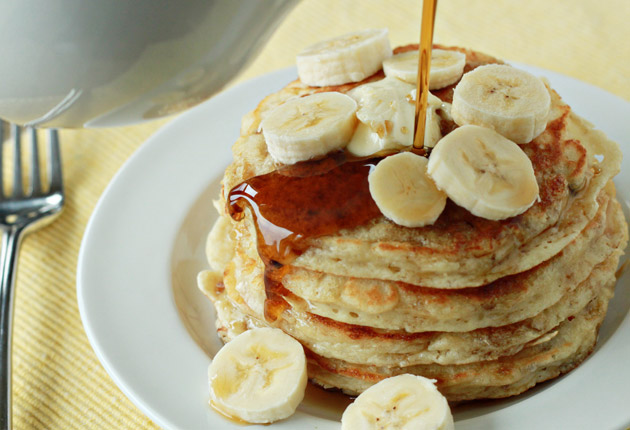 Stack of fluffy banana pancakes with banana slices and maple syrup being drizzled over the top