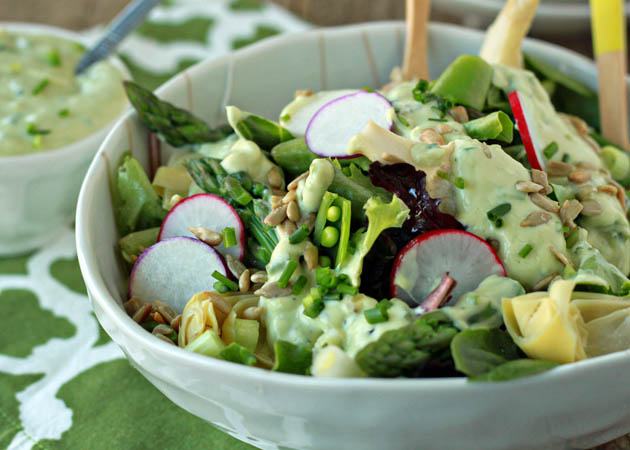 Spring Veggie Salad with Creamy Avocado Ranch - A simple bed of spring baby greens holds sugar snap peas, sliced scallions, tender asparagus, tangy marinated artichoke hearts, and snappy radishes. A drizzle of garlicky avocado ranch and a sprinkle of sunflower seeds completes the scene.