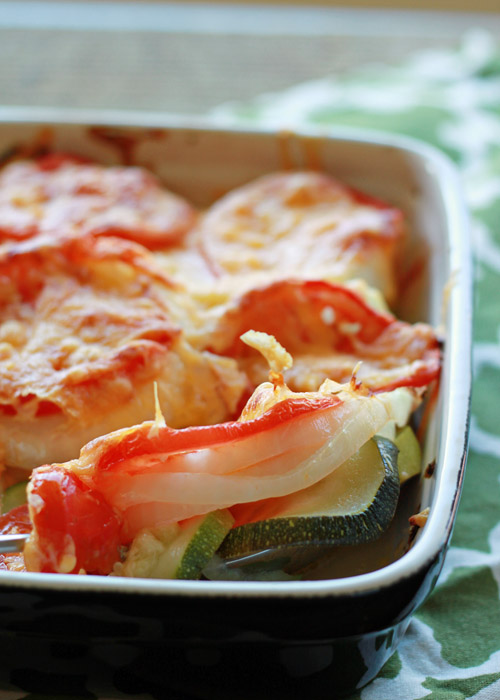 Mom's Cheddar Zucchini, Tomato, & Onion Gratin recipe - so easy! The quintessential summer side. Fresh-from-the-garden zucchini, tomatoes, and onions layered and covered with cheddar, then baked until tender and cheesy. Vegetarian with vegan option.