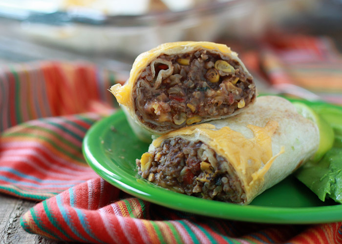 Roll up a few of these easy refried bean burritos, bake 'em up, and eat them now or freeze individually for super-easy lunches and dinners down the road. And with brown rice and only a small amount of cheese, they're overall a pretty darn healthy choice, too. Can be easily made vegan, vegetarian, or meaty. #freezerburritos #vegetarian