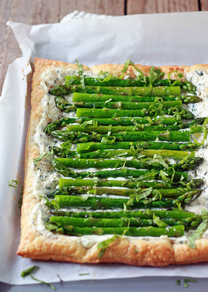 Asparagus Cream Cheese Tart recipe - Tender asparagus and tangy basil cream cheese top golden puff pastry in this easy vegetarian tart. Got carnivores too? Just top individual squares with crumbled bacon for the meat-eaters.