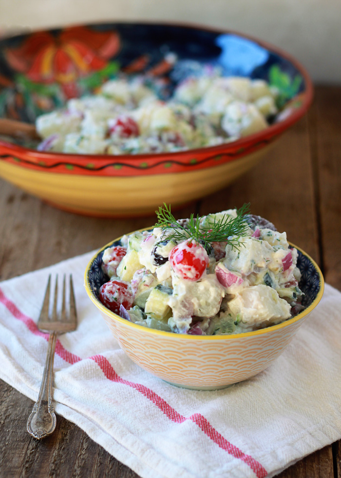 Creamy Greek Potato Salad recipe - Garlicky Greek yogurt tzatziki sauce forms the creamy base of this potato salad; a healthier, more protein-packed spin on the traditional mayo. Add kalamata olives, cherry tomatoes, red onions, and cucumber for fun and refreshing potato salad alternative.