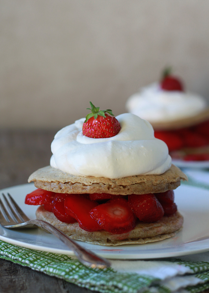 Easy! Strawberry Shortcake Pancakes recipe - fluffy buttermilk pancakes stacked with juicy strawberries and fresh whipped cream.