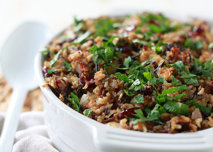 Herbed Wild Rice and Quinoa Stuffing - Specked with fresh herbs, apples, cranberries, and pecans, everyone will love this flavor-filled stuffing - and nobody will guess its little secret: it's vegetarian, vegan, and gluten-free!