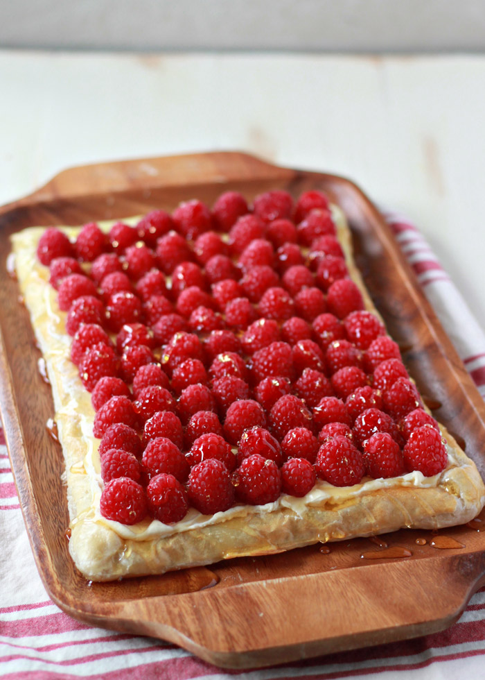 Fresh Raspberry Cream Cheese Puff Pastry Tart - Lush raspberries atop a fluffy lemon-vanilla cream cheese filling and a buttery golden puff pastry crust. This easy tart is sure to impress the guests at the holiday table. Only you need to know how easy it was to whip up!