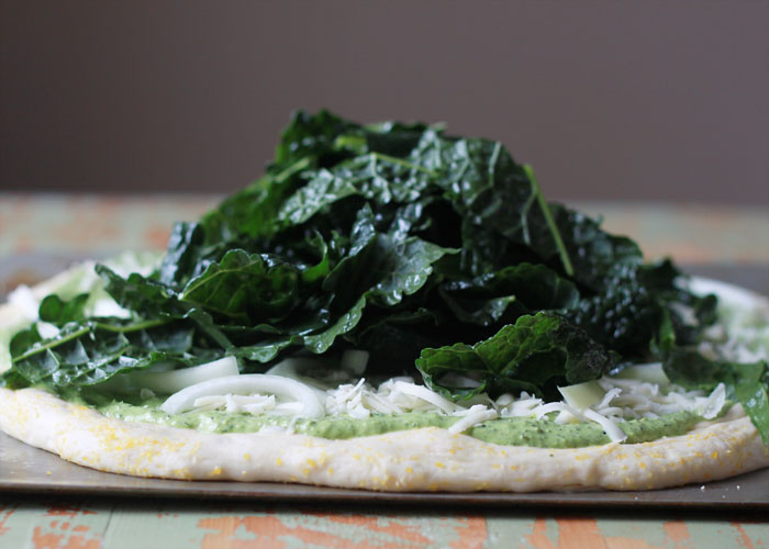 Kale & Pomegranate Pizza with Creamy Pesto Sauce recipe. Two doses of kale - both in the creamy, garlicky pesto and piled on top - make this vegetarian pizza a green powerhouse (in the most delicious way, promise!) Top with ruby-red pomegranate arils for color and a little irresistible sweet and salty contrast.