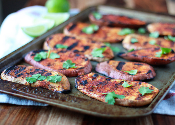Sweet and Smoky Grilled Sweet Potatoes with Cilantro and Lime - Sweet potatoes on the grill? Heck yes! Thin-sliced sweet potato slabs grill up tender and perfect on the BBQ. Rub 'em with spices and top with cilantro and lime for the side of the summer.