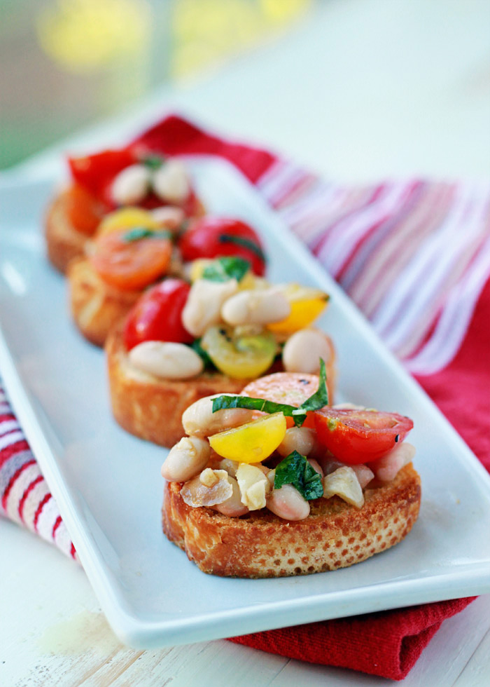 Cherry Tomato and White Bean Bruschetta - Fresh tomatoes and creamy white beans tossed with basil, balsamic, and loads of garlic, then loaded onto crunchy golden toasts. So pretty much the tastiest appetizer recipe in the history of the land.