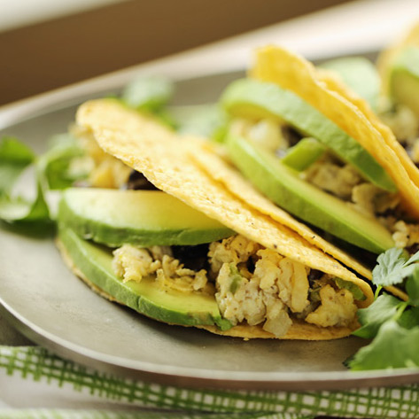 Scrambled eggs flecked with veggies and black beans, stuffed into a crunchy taco shell and topped with creamy avocado. These grab-and-go breakfast tacos are ready in 10 minutes flat! Gluten-free, dairy-free, and vegetarian (but with options for everyone!)