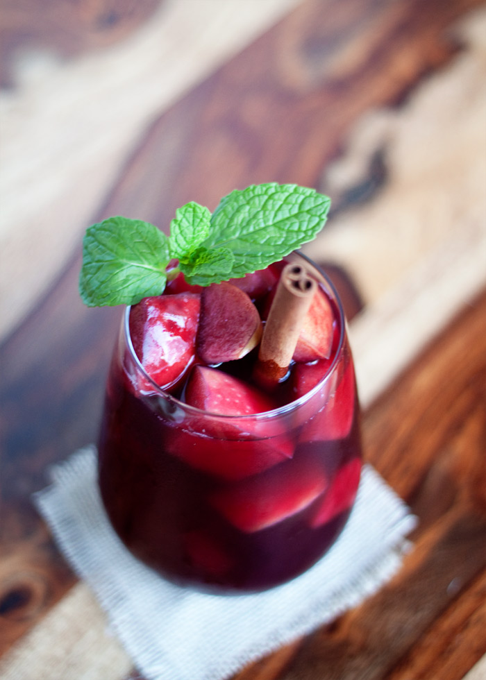 Juicy Red Apple Sangria recipe - A lush red sangria with apples, spices, brandy, and more. We love this sangria for the holidays.
