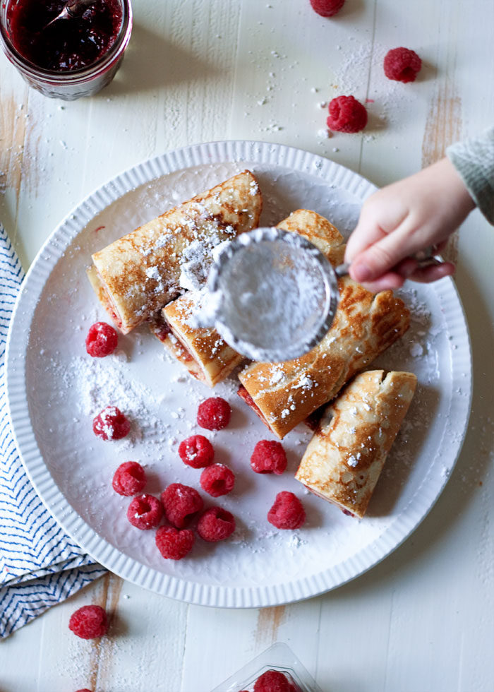 Swedish Pancakes recipe - Just 5 simple ingredients and you're on your way to real Swedish pancakes. Rich, tender, & totally delicious with a smear of butter and jam. (Non-dairy option) Perfect to make with kids! #cookingwithparents