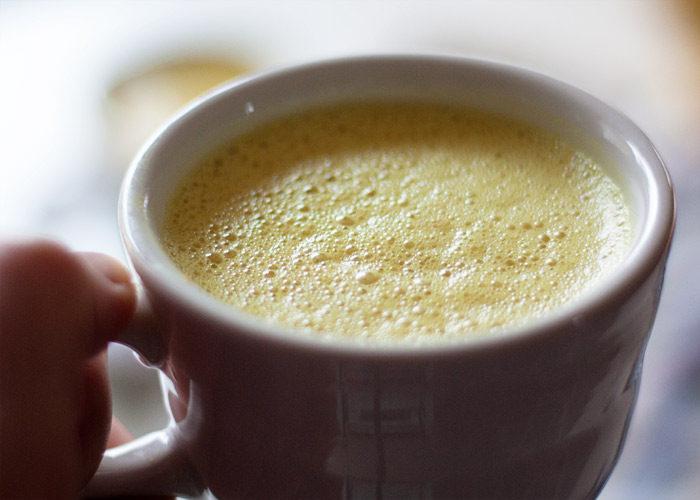 Hand holding a mug of golden milk