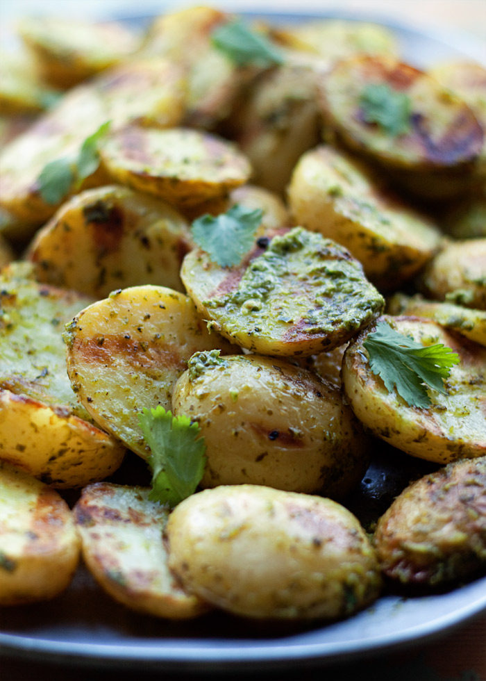 Grilled Baby Potatoes with Mojo Verde Sauce - Tender potatoes grilled until golden and tossed with a spicy cilantro-serrano pepper sauce. Such a fun side dish for spring and summer. Vegan, gluten-free.