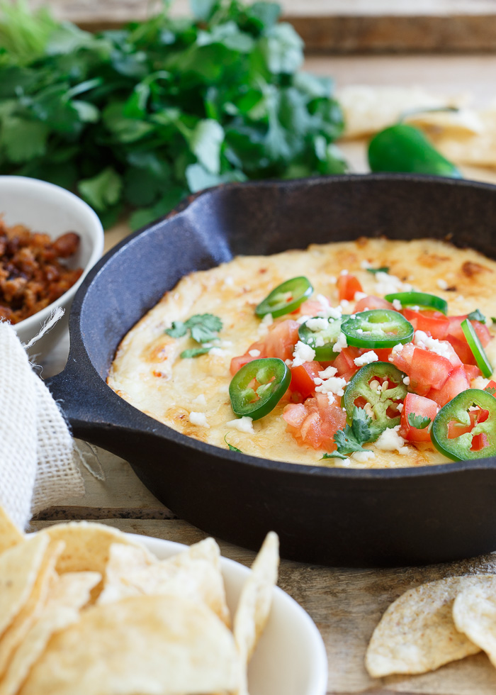 Lightned-Up Queso Fundido Recipe (with hidden cauliflower!) - A lightened-up queso fundido with only 1/3 the cheese! All the creamy cheesiness you love of the classic Mexican dish, made healthier with a hidden veggie boost. Vegetarian with omnivore option (top the carnivores' portions with cooked chorizo for a meaty version.)