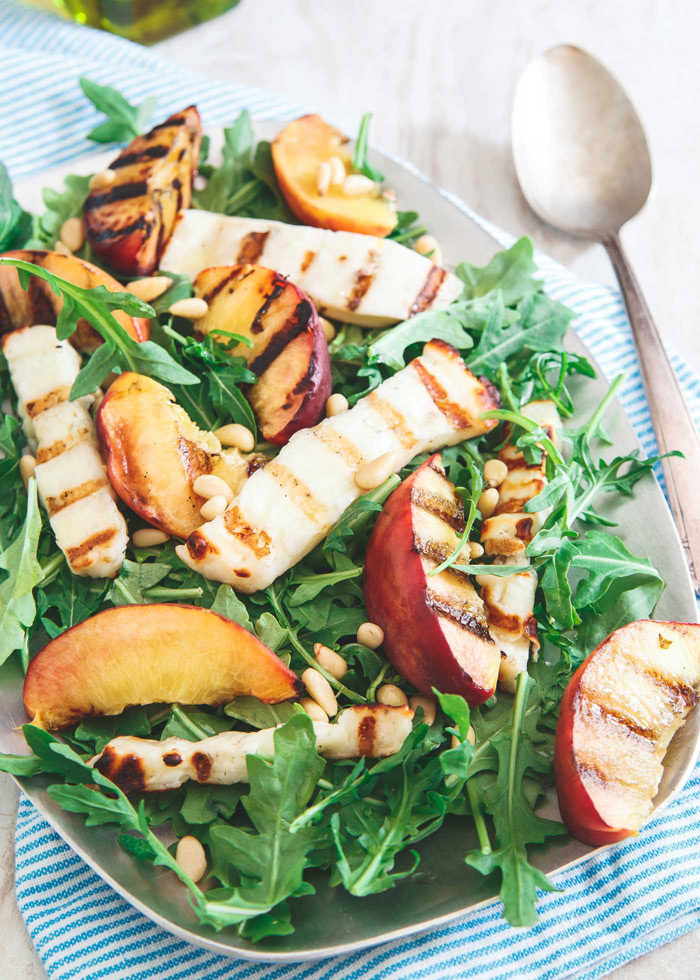 Grilled Halloumi & Peach Salad - Grilled halloumi, juicy peaches, and fresh arugula in this Grilled Halloumi & Peach Salad means you get a salty, sweet and zesty element all in one light bite. Vegetarian.