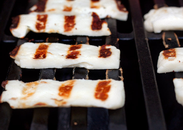 Slices of warm halloumi being cooked on the grill