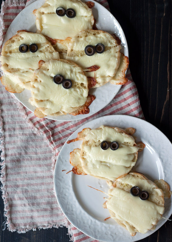 "Garlic Cheese English Muffin Mummies - fun Halloween snack idea! These cute ""mummies"" are made super-simply with English muffins, string cheese, and olives. A quick brush with garlicky olive oil adds flavor. Garlic-cheesy mumminess!"