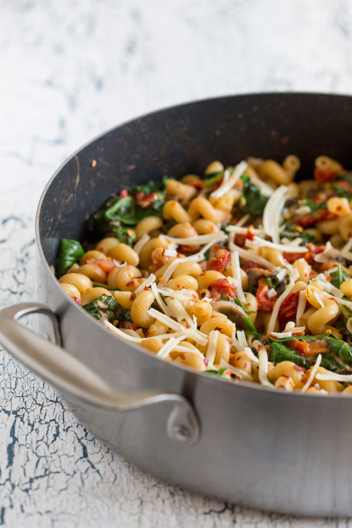 One-Pot Pasta Florentine recipe - This creamy pasta is loaded up with spinach, tomatoes, and Asiago cheese. Just 20 minutes from cutting board to table - and only one pot to clean! Vegetarian with chicken option.
