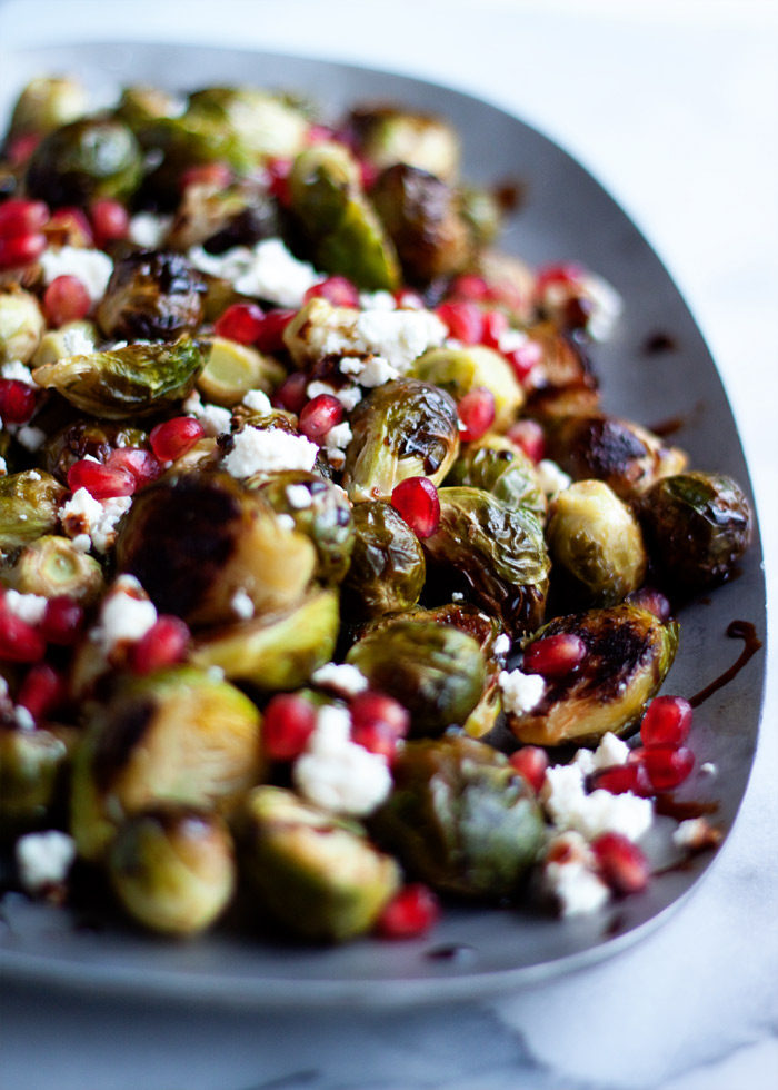 Roasted Brussels Sprouts with Pomegranate & Feta recipe - Tender caramelized sprouts baked to perfection and topped with the sweet crunch of pomegranate seeds and salty feta. The perfect holiday side dish! Vegetarian with vegan option.