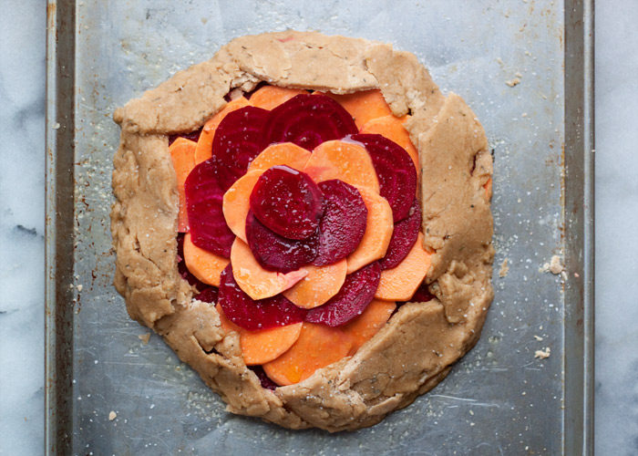 Rustic Sweet Potato & Beet Galette with Sea Salt & Herb Coconut Oil Crust vegan recipe - Thinly sliced sweet potatoes and ruby-red beets top a tender sea salt and herb coconut oil crust. This vegan entree is definitely worthy of a spot at your holiday table - and the best part is you don't have to worry about making it look perfect. The more rustic the better!