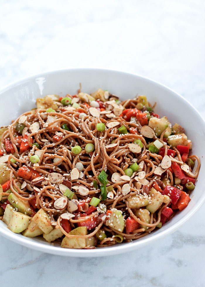 Veggie-Loaded Sesame Almond Butter Noodles - This cold pasta salad is packed with refreshing cukes, carrots, sweet bell peppers, and scallions - then drenched in a creamy almond-butter sesame dressing. Make it ahead of time for easy lunches, dinners, or picnic and potluck fare. Vegan with gluten-free option.