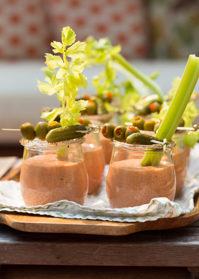 Gazpacho, cocktail style! This Bloody Mary Gazpacho is served up in shooters with a black pepper rim and loads of garnishes. Perfect #vegan #summerappetizer.