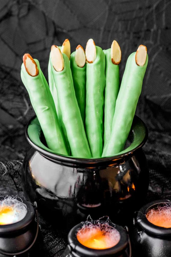 Come hither, my pretties! Here are 10 Witch Finger Snack Ideas - enough to count on both hands. Breadsticks, cookies, candy pretzels, and more including these Witch Finger Pretzels from @homemadehooplah. #witchesfingers #halloweensnacks #halloween