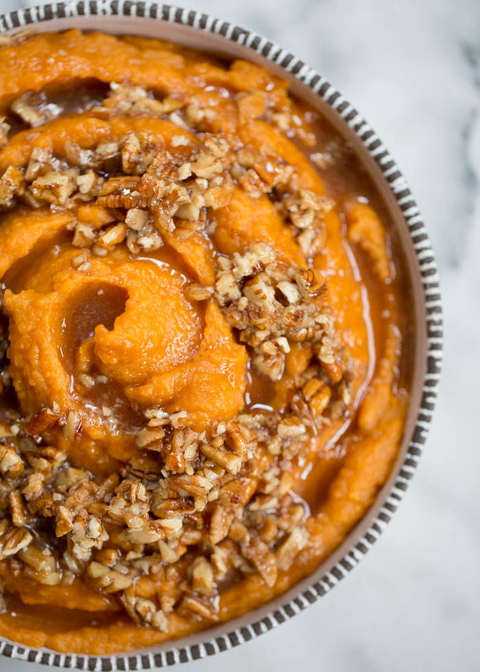 Sweet potatoes simmered in coconut milk until tender, whipped until smooth, and topped with a warm maple syrup and pecan mixture. Dairy-free and delicious! #veganthanksgiving #veganthanksgivingsides #sweetpotatoes #dairyfreethanksgiving