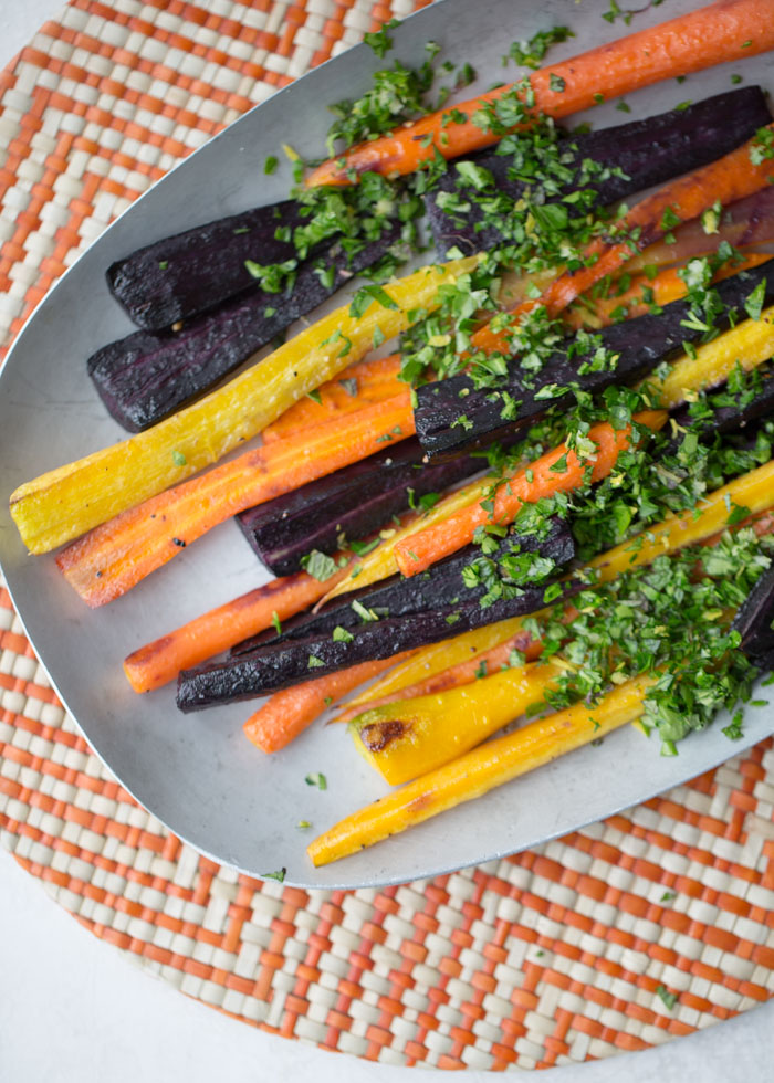 Roasted Rainbow Carrots with Mint Gremolata - Colorful roasted carrots topped with a bright and zippy herb garnish. Super easy and impressive too! For the gremolata, a Microplane zester makes quick work of the grated garlic and lemon zest. #roastedcarrots #eastersidedish