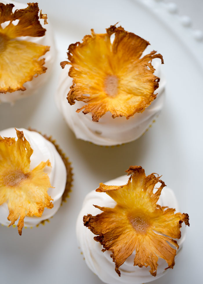 How to Make Dried Pineapple Flower Garnishes for cupcakes, cakes, cocktails and more. Paper-thin pineapple slices, oven-dried into yellow-flower perfection. Easy-to-follow, step-by-step instructions with photos showing exactly how to make these beauties.