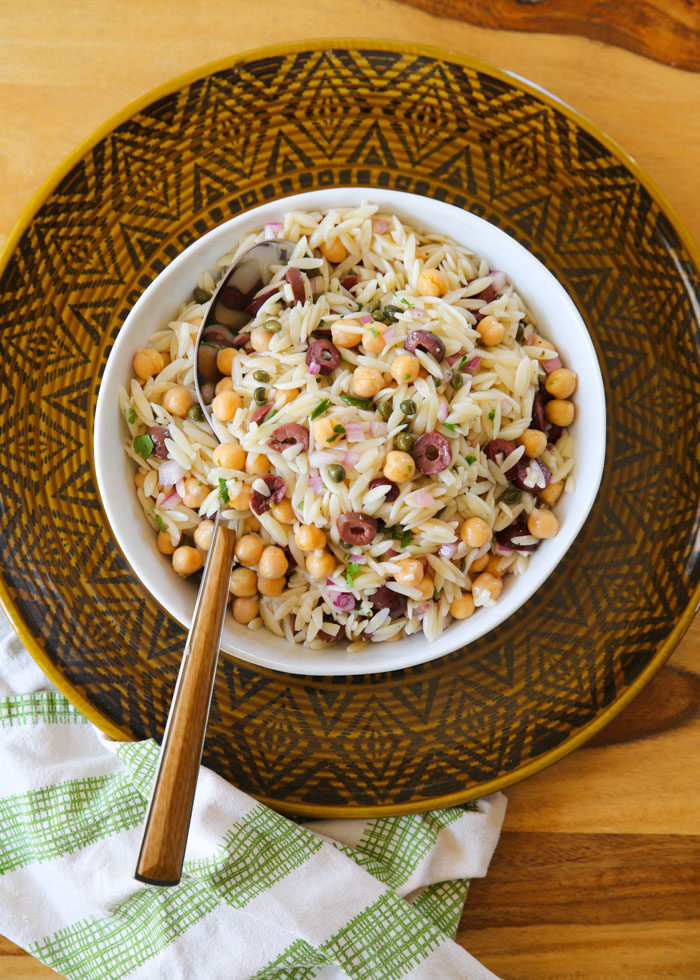 Greek-ish Orzo Salad with Chickpeas, Olives, & Capers - A simple pasta salad with loads of flavor, and hearty enough to stand in as a main dish. The perfect potluck salad - or stick some in a mason jar for an easy portable lunch!