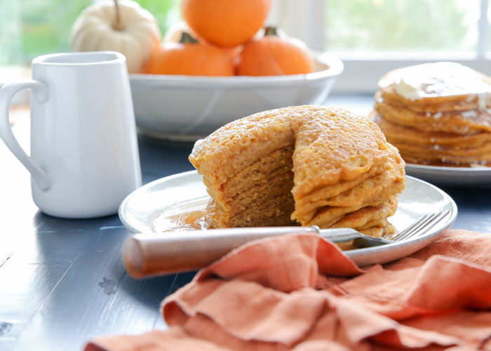 Fluffy Vegan Pumpkin Pancakes - Tall, fluffy, and tender. These vegan pancakes are loaded with pumpkin, spice, and everything nice. Arguably even better than traditional pumpkin pancakes - try them and see!