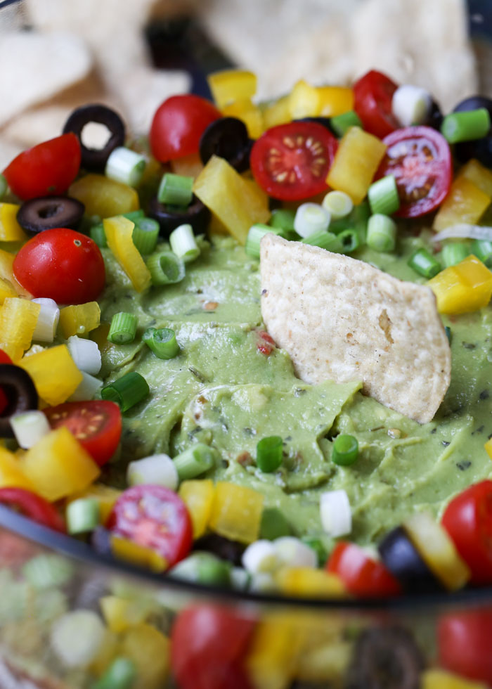Vegan 7-Layer Bean Dip - Who needs cheese when you have creamy guacamole and tangy vegan sour cream? Not us! This decked-out bean dip is the perfect appetizer for vegans or non-vegans alike. (My carnivorous guy LOVES it!)