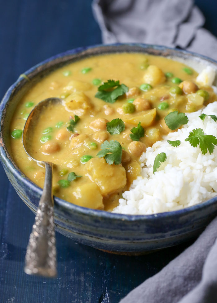 Slow Cooker Chickpea Red Lentil Curry - A creamy curry with coconut milk, potatoes, and peas. Scoop over rice and it's a full meal! Only 15 minutes hands on time. A weeknight winner! #veganslowcooker #chickpeacurry