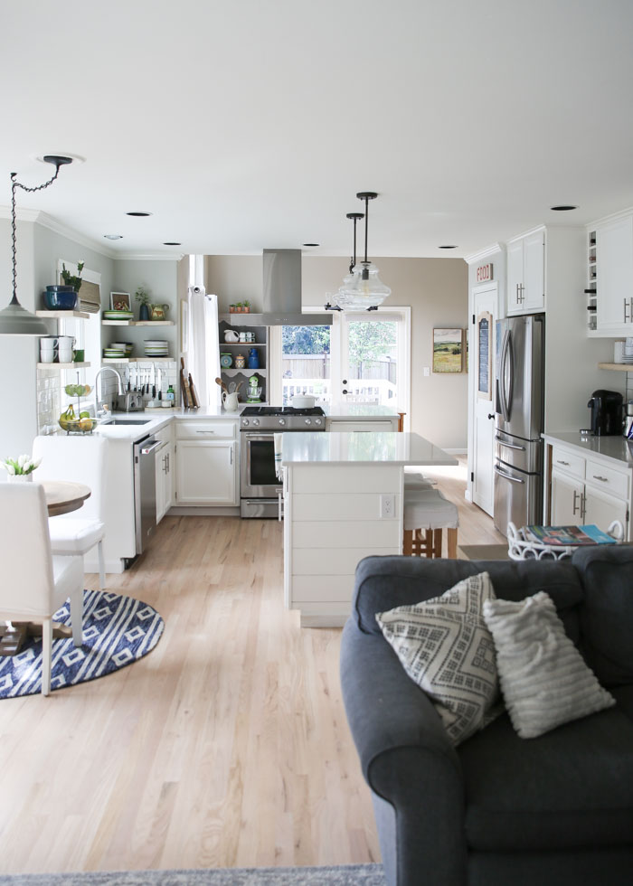 Budget-friendly white kitchen remodel. White quartz countertops, painted cabinets, whitewashed wood floors