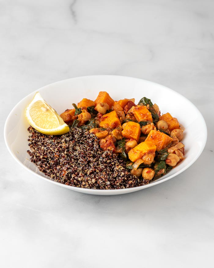 Moroccan Inspired Sweet Potato & Spinach Stew - This vegan stew is rib-sticking and warmly spiced. Thick with chickpeas, sweet potatoes, tomatoes, and spinach - so satisfying with a scoop of brown rice.